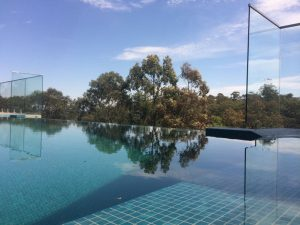PFI-Glass-frameless-glass-installed-with-stand-off-pins-on-an-infinity-edge-pool-300x225